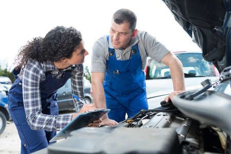 mechanics conferring while looking at car engine
