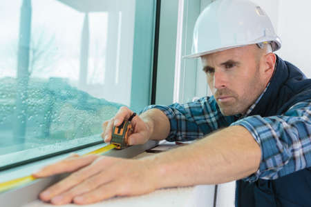 worker measuring the window length