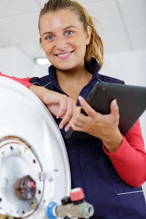 portrait of happy female plumber working on central heating boiler Banque d'images