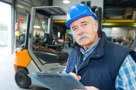 senior worker with a clipboard working on a forklift