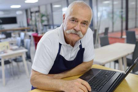 portrait of a senior man with laptop