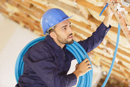 builder threading cables through wall Stock fotó