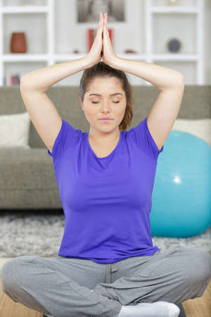 a woman practicing home yoga Standard-Bild