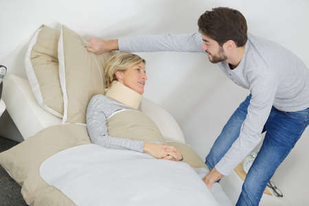 son helps his mum suffering with a cervical collar