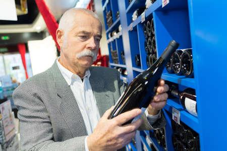 man in a supermarket chossing wine bottles