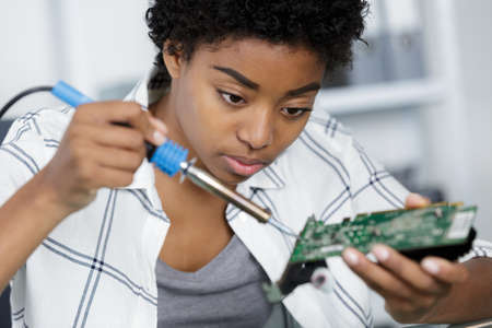 pretty young woman soldering computer pc motherboard in workshop