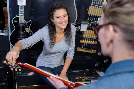 Two women looking at guitar Stock Photo