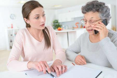 Nieta enseñando a la abuela a usar el teléfono inteligente