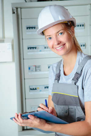 a female worker reading the electrical meter Imagens