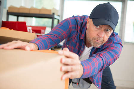 Man is moving a heavy box Stock Photo - 133295764