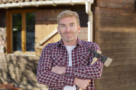 handsome man posing in front of wooden hut holding axe