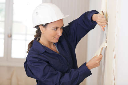 Woman removing wall paper