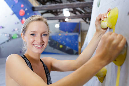 Active happy woman in the artificial climbing wall