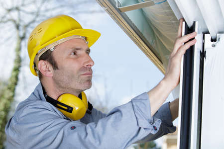 handyman repairs window with screwdriver Stock fotó