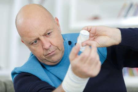 man plastering his own wrist