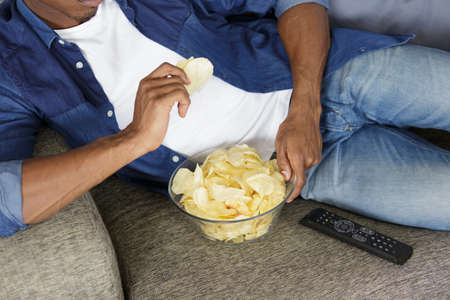 man watching tv and eating chips Zdjęcie Seryjne