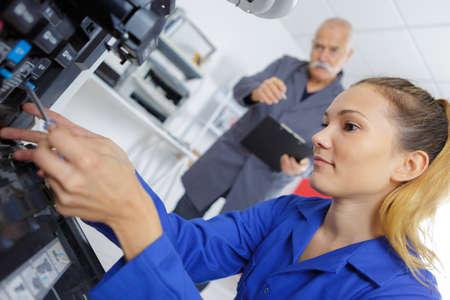 female technician fixing a printer