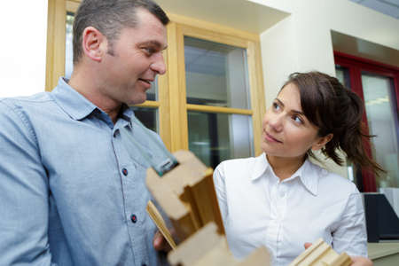 sales assistant showing window samples to customer