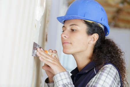 female plasterer removing an old plaster