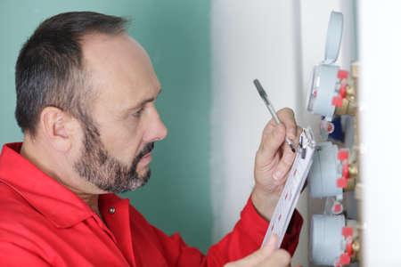 man measuring tire pressure with meter Reklamní fotografie