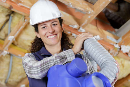 happy female worker holding ventilation pipes