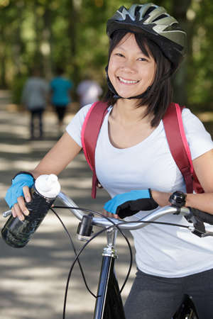 an asian woman cyclist smiling