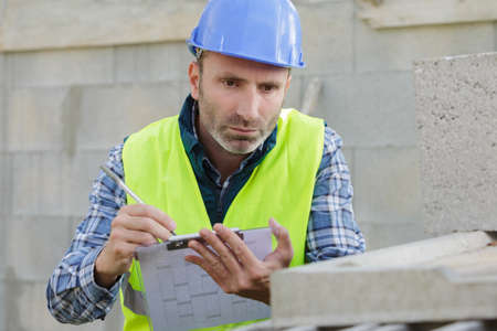 portrait of a builder writing on clipboard Stock Photo
