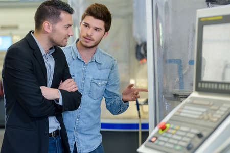 man and apprentice working on printing machine