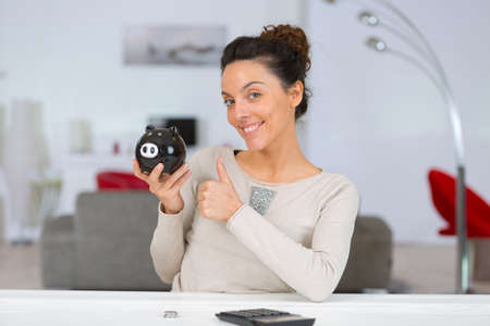happy woman showing thumbs up after counting money