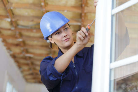 a woman is fixing a window