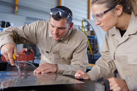 male and female engineers inspecting metal part