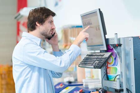 man operating computerised machne to mix paint 免版税图像
