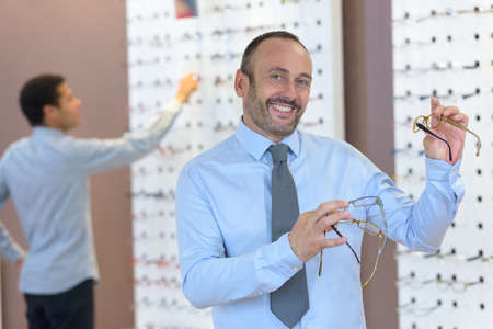 man choosing glasses in optics store