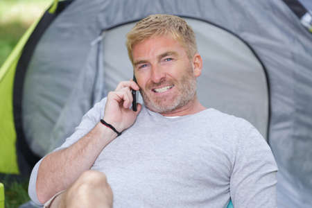 mature man using smartphone by tent on campsite