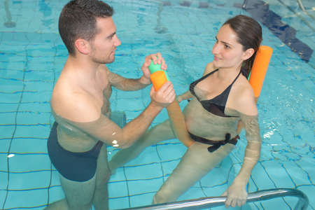 young pregnant woman with the husband in the pool 写真素材