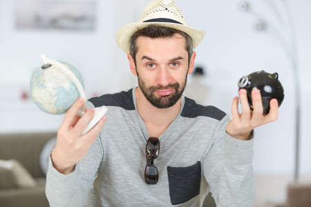 man holding globe and piggy bank in each hand