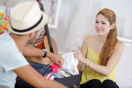 young couple packing clothes for trip