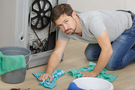 frustrated man cleaning under sink pipe leakage