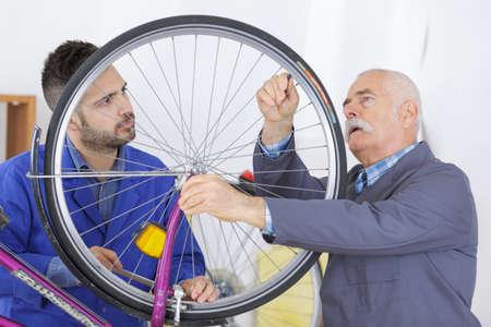 bicycle mechanic and apprentice repairing a bike in workshop