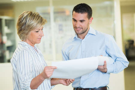 mature woman showing papers to male colleague in office Banco de Imagens