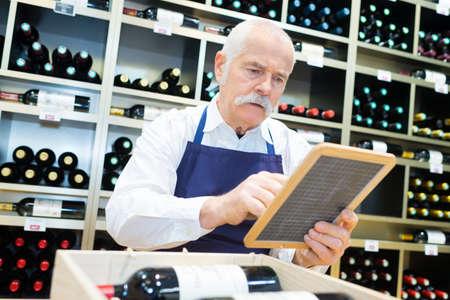 senior winemaker writing on board 版權商用圖片