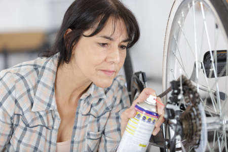 female mechanic repaired bicycle in a workshop