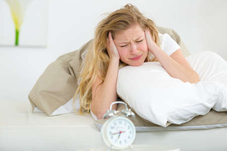annoyed woman in the morning with her ringing alarm clock Stock fotó