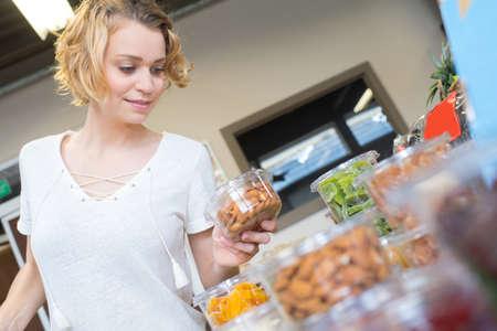 smiling female customer choosing confiture in food store