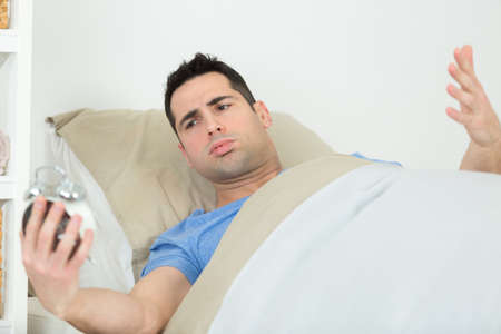 tired man in bed not happy with alarm clock