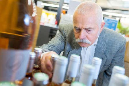 senior man choosing bottle of wine