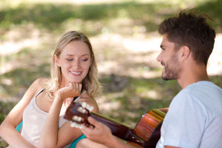 man playing guitar for young lady sat in park Archivio Fotografico