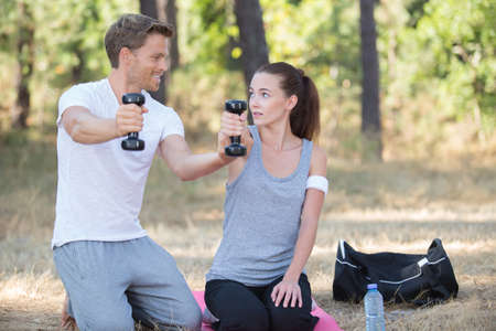 couple training in nature with dumbbells