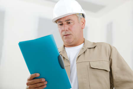 man builder looking at clipboard