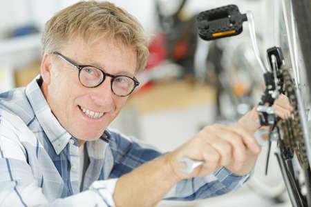 happy older man repairing a bicycle wheel